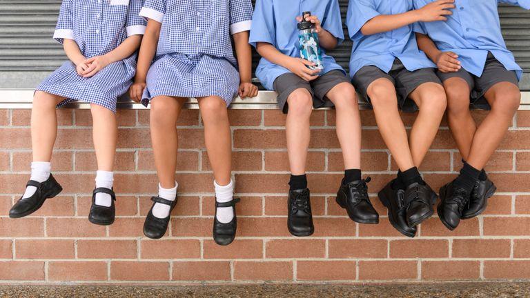 Low section view of five school children sitting on brick wall wearing school uniform - Stock image