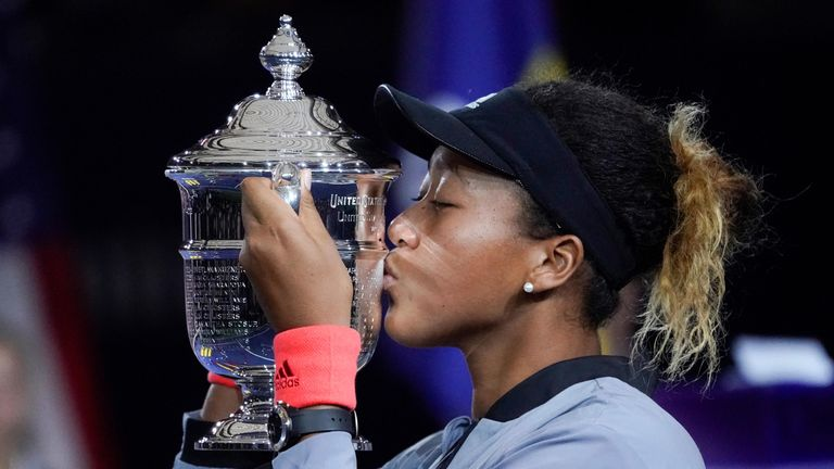Naomi Osaka of Japan holds the U.S. Open trophy after beating Serena Williams of the USA