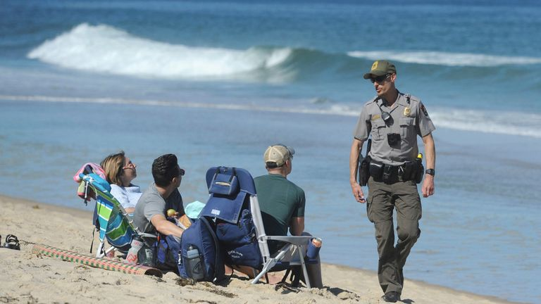 Cape Cod National Seashore Park Ranger Eric Trudeau walks up to a group of beach visitors telling them that the beach is closed to swimming. He was walking up and down the beach alerting people to the beach closure. .A person was bitten by a shark off Newcomb Hollow Beach Saturday