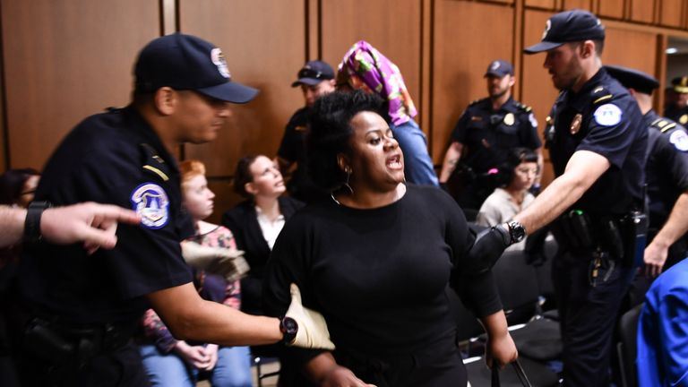 A protester is led away from the confirmation hearing