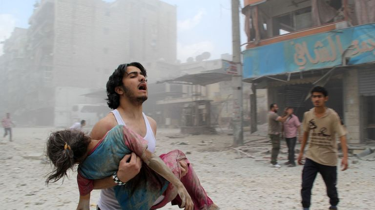 A man carries a girl injured in a reported government forces bomb attack in Aleppo in June 2014