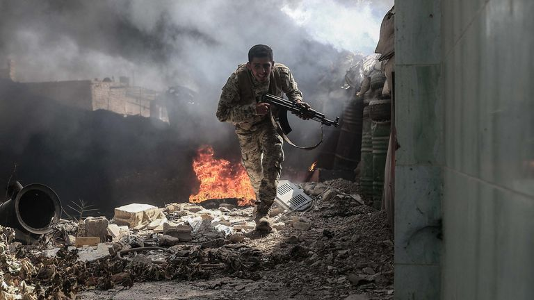 A fighter from Jaysh al Islam runs to avoid sniper fire in Douma
