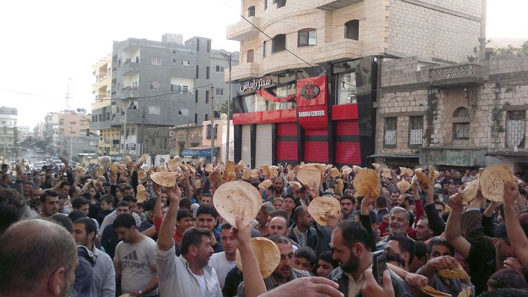 Syrians hold up bread during an anti-government protest in Banias, a northern port