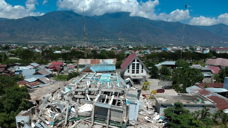 This aerial picture shows the remains of a ten-storey hotel in Palu in Indonesia's Central Sulawesi on September 30, 2018 after it collapsed following a strong earthquake in the area. - The death toll from the powerful earthquake and tsunami in Indonesia rose to 420 on September 30, as stunned people on the stricken island of Sulawesi struggled to find food and water, looting spread and fears grew that whole towns had still not been heard from. (Photo by Azwar / AFP) (Photo credit should read AZ