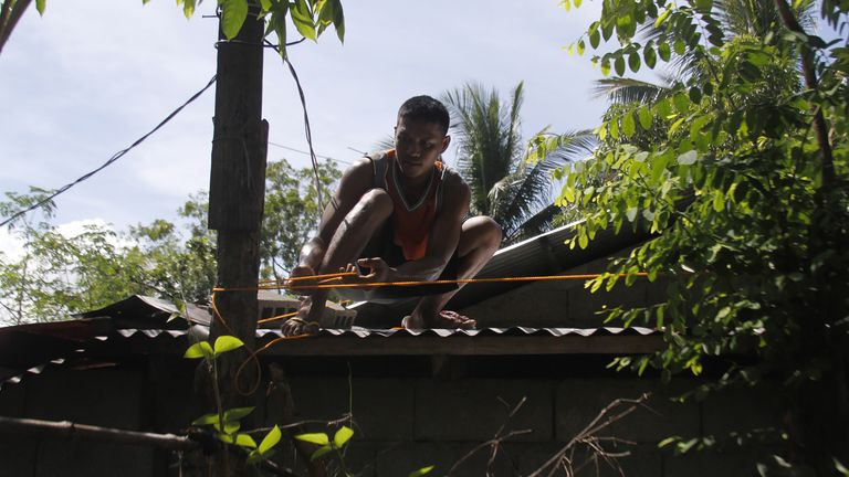 A man secures the roof of his house in Candon City, north of Manila