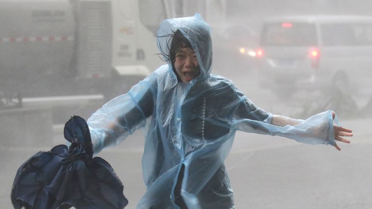 A woman runs in Shenzen as Typhoon Mangkhut arrives in China