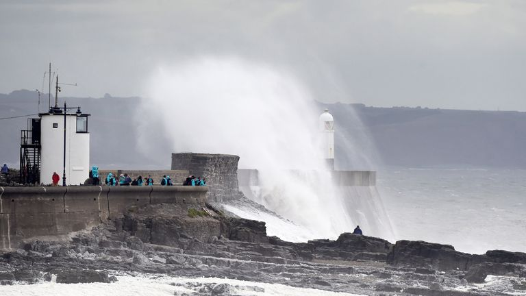 Waves crash over the lighthouse at Porthcawl in Wales