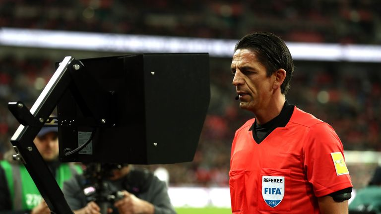 Referee Deniz Aytekin checks the VAR during the England-Italy friendly at Wembley in March