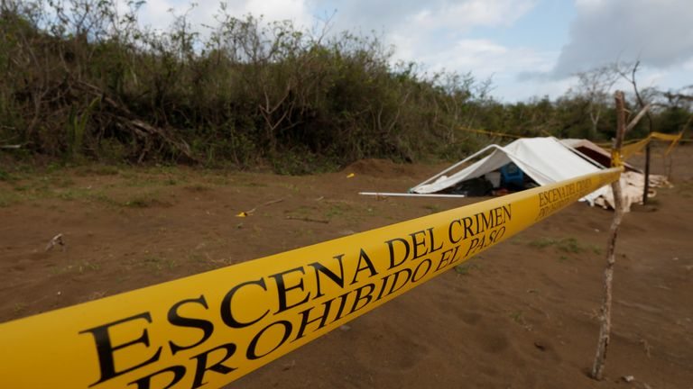 A police cordon marks the perimeter of the site where a forensic team and judicial authorities work in unmarked graves where skulls were found, on the outskirts of Veracruz