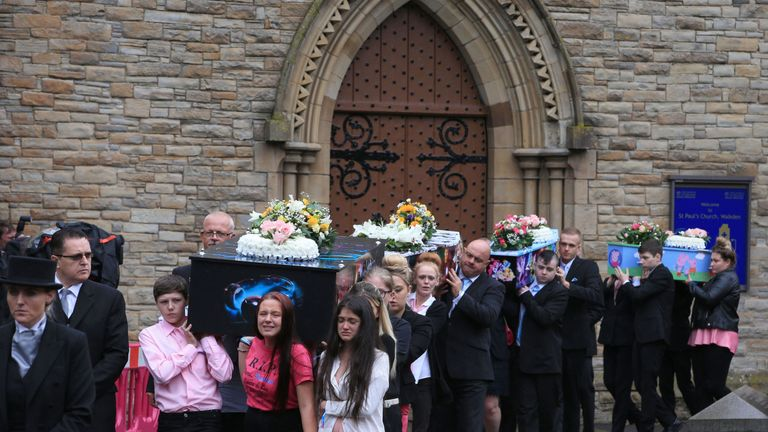 The coffins are carried from the church