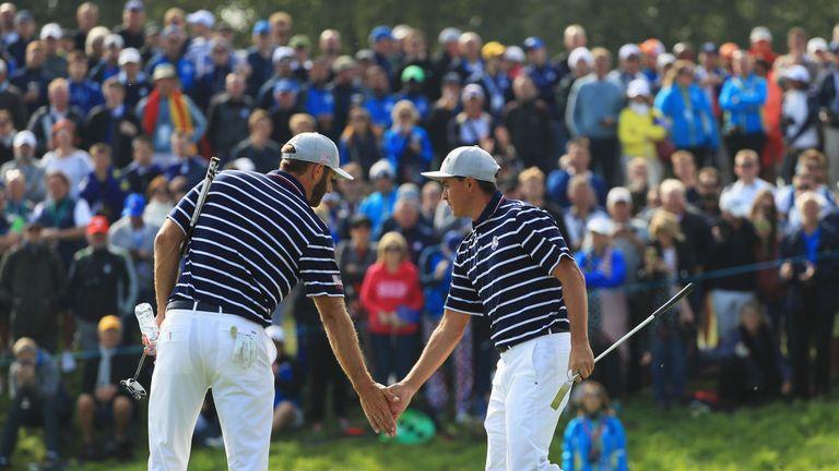 Dustin Johnson of the United States and Rickie Fowler of the United States shake hands during the morning fourball matches of the 2018 Ryder Cup at Le Golf National on September 28, 2018 in Paris, France.