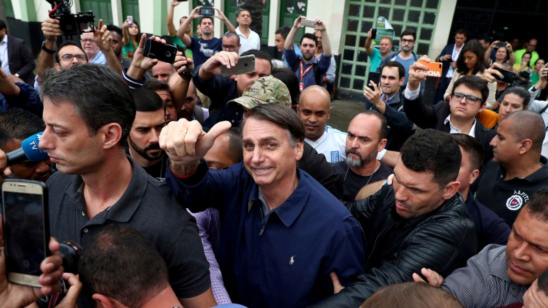 Jair Bolsonaro, pictured centre after casting his vote, was stabbed while campaigning