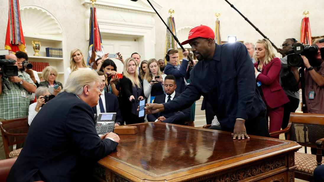 Kanye West shows Donald Trump his mobile phone in the Oval Office
