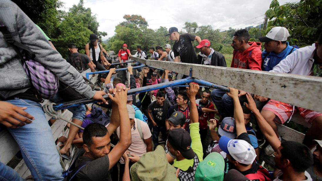 Caravan migrants break Guatemala border fence, rush Mexico
