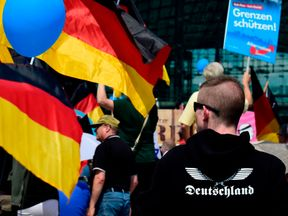 Alternative for Germany (AfD)'s demonstrators holding AfD and German flags gather at the main station in Berlin to attend the 'demonstration for the future of Germany' called by the far-right AfD in Berlin on May 27, 2018