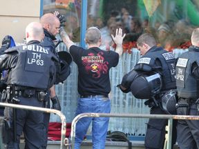 A reveller is checked by police on his arrival for a neo-nazi rock concert in Apolda