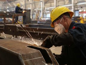 Worker welding truck parts at a factory in Weihai in China's eastern Shandong province