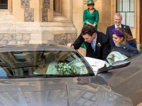 Jack Brooksbank helps his new wife into a Aston Martin DB10