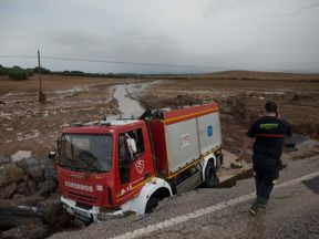 A Spanish firefighter died while emergency services responded to flash flooding