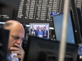 A trader sits next to a screen displaying a report on German Chancellor Angela Merkel and general elections in Germany, as he works at the stock exchange in Frankfurt am Main, western Germany, on September 25, 2017