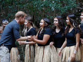 Prince Harry greets and shakes the hands  of the K'gari tribe