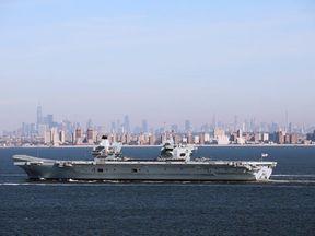 HMS Queen Elizabeth sails by the iconic Manhattan skyline