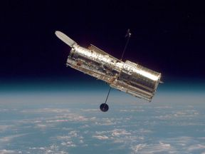 IN SPACE: (FILE PHOTO) In this handout from the National Aeronautical Space Administration (NASA), the Hubble Space Telescope drifts through space in a picture taken from the Space Shuttle Discovery during Hubble?s second servicing mission in 1997. NASA annouced October 31, 2006 that hte space agency would send a space shuttle to the Hubble Telescope for a fifth repair mission no earlier than May of 2008. (Photo by NASA via Getty Images)