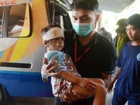 An injured child is carried by an Indonesian Red Cross officer