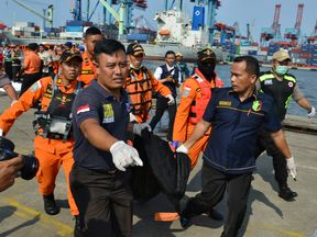 Rescue team members carry a body bag with the remains of a passenger of Lion Air flight