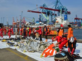Rescue team members arrange the wreckage, showing part of the logo of Lion Air flight JT610, that crashed into the sea, at Tanjung Priok port in Jakarta, Indonesia, October 29, 2018. REUTERS/Stringer