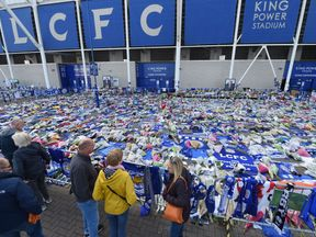 People pause at the tributes gathered outside Leicester City Football Club's King Power Stadium in Leicester, eastern England, on October 31, 2018