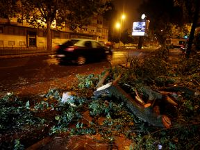 Tree branches litter a street in Benfica neigborhood as storm Leslie hits