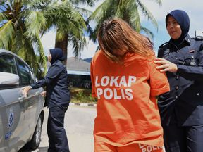 British national Samantha Jones is escorted by a police officer as she arrives at a court in Langkawi