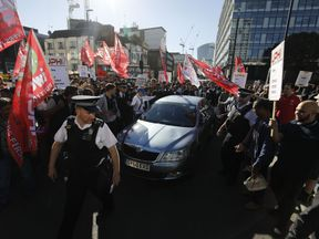 Drivers for taxi-sharing app Uber rally outside Uber's offices in London on October 9, 2018 with placards from the Independent Workers Union of Great Britain (IWBG) and United Private Hire Drivers (UPHD) calling for higher fares and improved workers' rights as they went on a 24-hour strike. - Drivers for taxi-sharing app Uber went on strike in Britain, demanding higher fares and improved workers' rights and urging users not to cross the digital picket line by ordering rides. Around 50 protesters