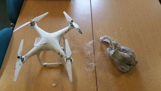 Undated handout photo issued by West Midlands Police of a drone and a bag of drugs which was seized after an attempt to smuggle the drugs into a prison. PRESS ASSOCIATION Photo. Issue date: Friday October 26, 2018. Thirteen members of a drug smuggling gang were sentenced for attempting to airlift £500,000 worth of drugs into prisons throughout the UK. See PA story COURTS Drones. Photo credit should read: West Midlands Police/PA Wire NOTE TO EDITORS: This handout photo may only be used in for edi