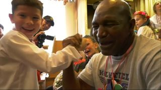 Former boxing world champion arm wrestles with a boy while visting Children's home.