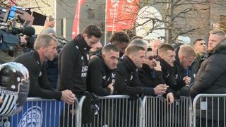 The team join the chairman's family to observe the tributes