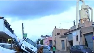 Cars are piled up where flood waters left them in Majorca