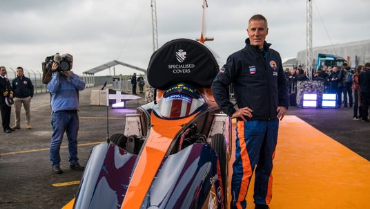 Royal Air Force Wing Commander Andy Green poses for a photograph next to the Bloodhound supersonic car as it is prepared for a test run at the airport on October 26, 2017 in Newquay, England.