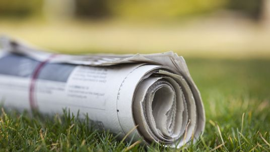 Newspaper on green grass outdoors background
