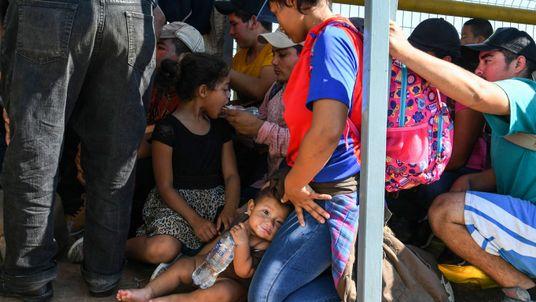 Honduran migrants wait to cross the border from Ciudad Tecun Uman, Guatemala, to Ciudad Hidalgo, Mexico