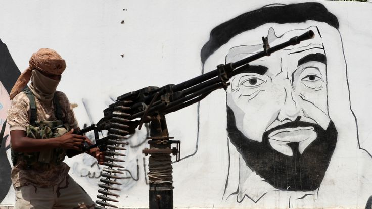 A pro-government soldier passing by a mural of the late UAE founder Sheikh Zayed bin Sultan al-Nahyan in the city of Mukalla