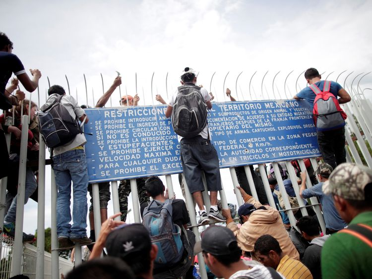 A group attempt to scale a fence into Mexico