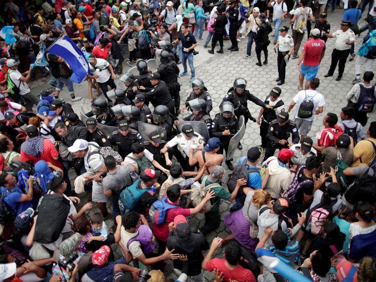Honduran migrants storm a border checkpoint to cross into Mexico, in Tecun Uman, Guatemala