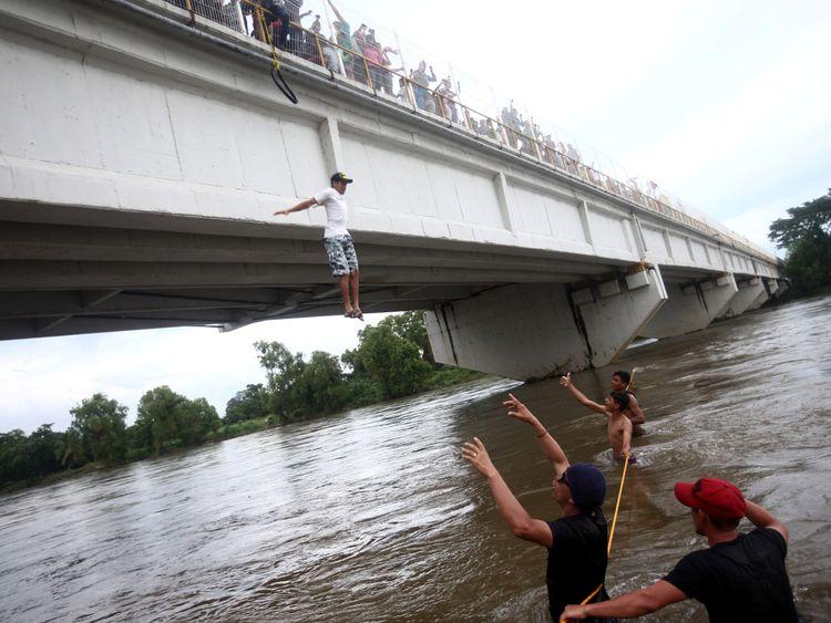 A Honduran jumps from a bridge to avoid a Guatemala-Mexico border checkpoint