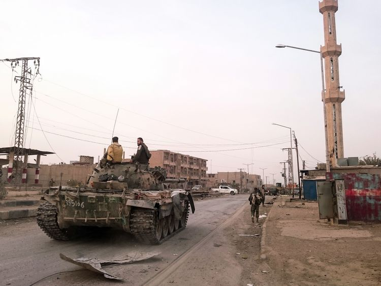 Pro-Syrian government forces ride on a tank in Abu Kamal