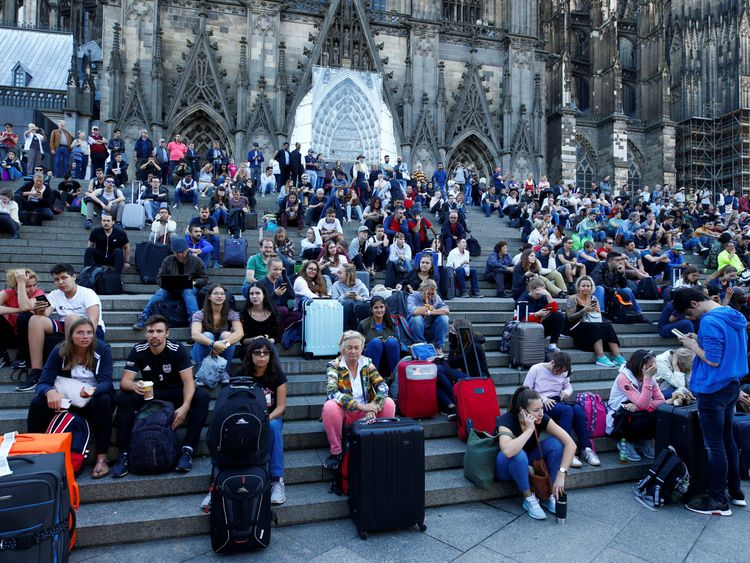 Passengers wait outside the main train station in Cologne, Germany