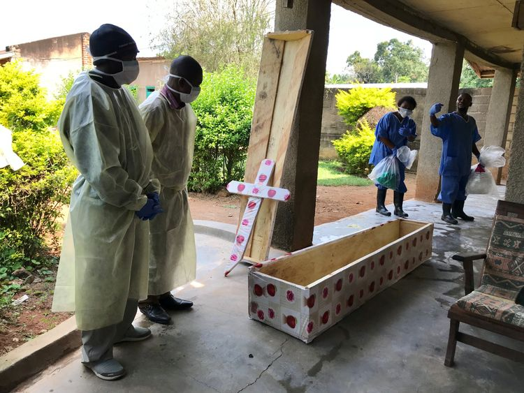 Health workers conduct a safe burial of an Ebola victim in Beni in August