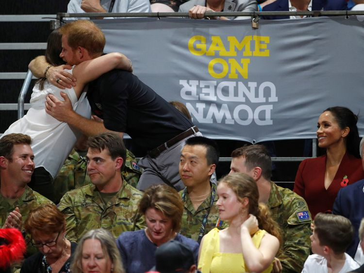 Britain's Prince Harry hugs a spectator as Meghan, Duchess of Sussex, looks on during the Invictus Games Sydney 2018 wheelchair basketball gold medal match at Quaycentre in Sydney, Australia October 27, 2018