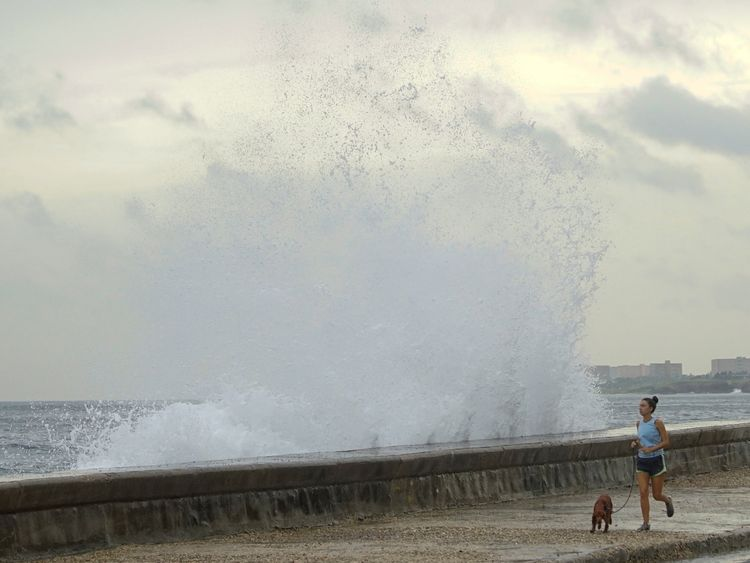 A woman jogs with a dog as waves splash at the seafront in Havana, after Hurricane Michael passed in western Cuba, October 9, 2018